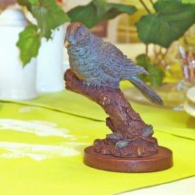 Bronzen vogeltje op tak